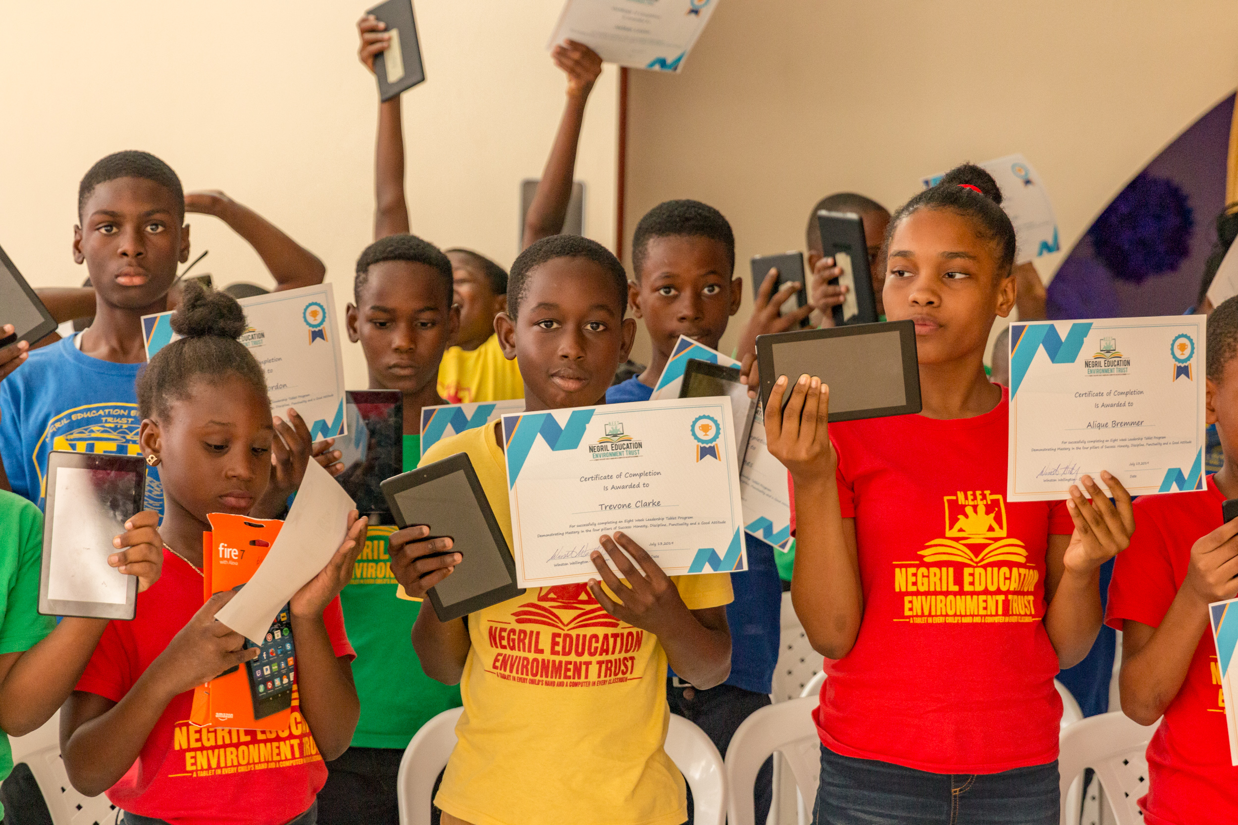 Graduating students holding up their certificate and tablets