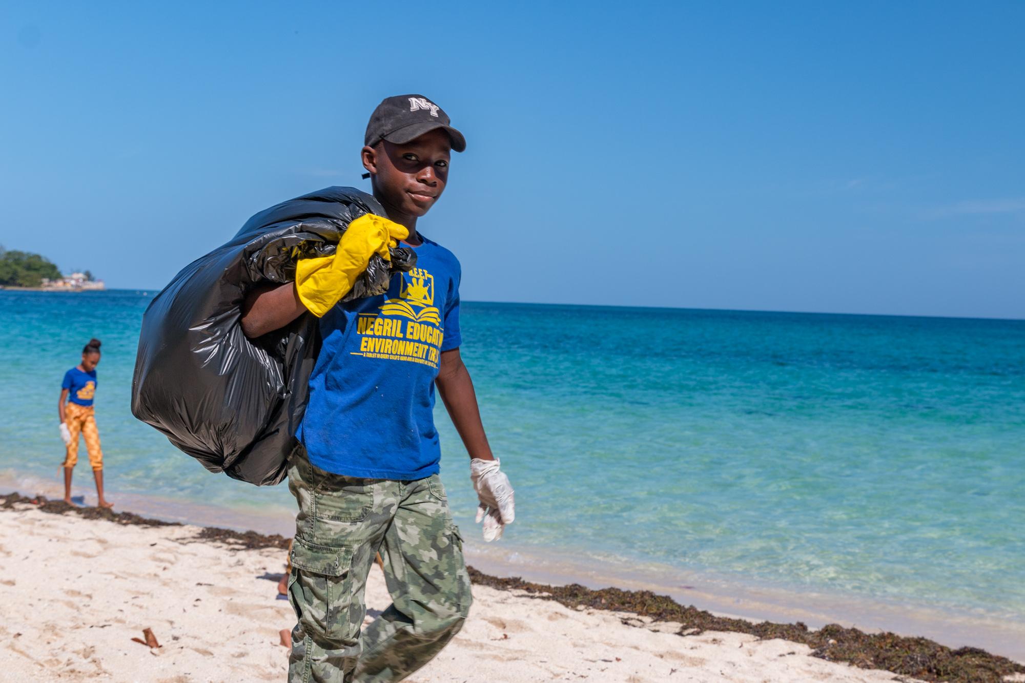 Student hauling garbage bag