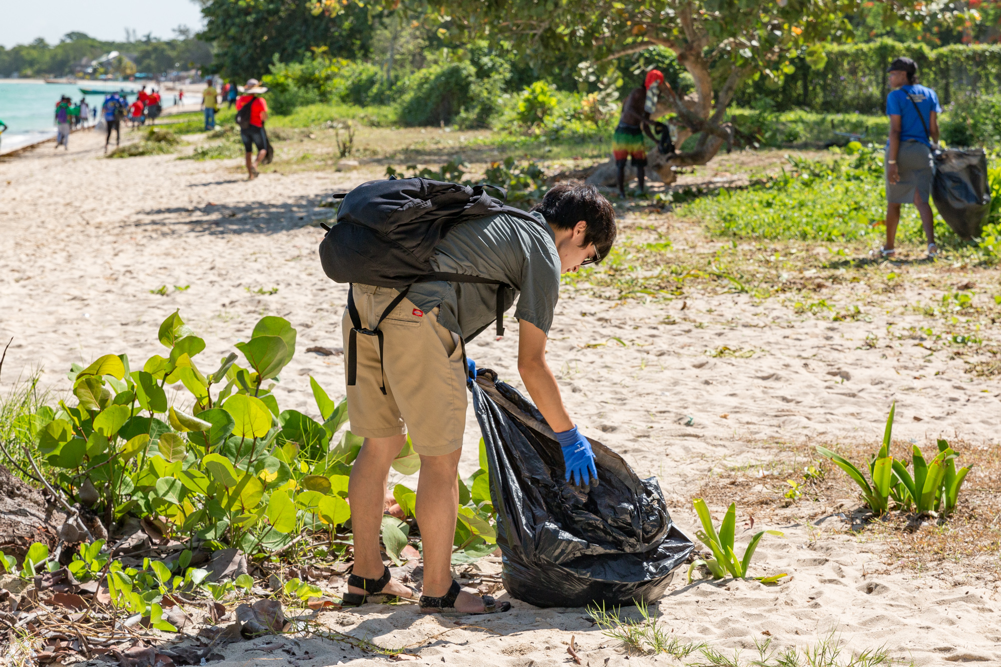 Volunteer filling garbage bag