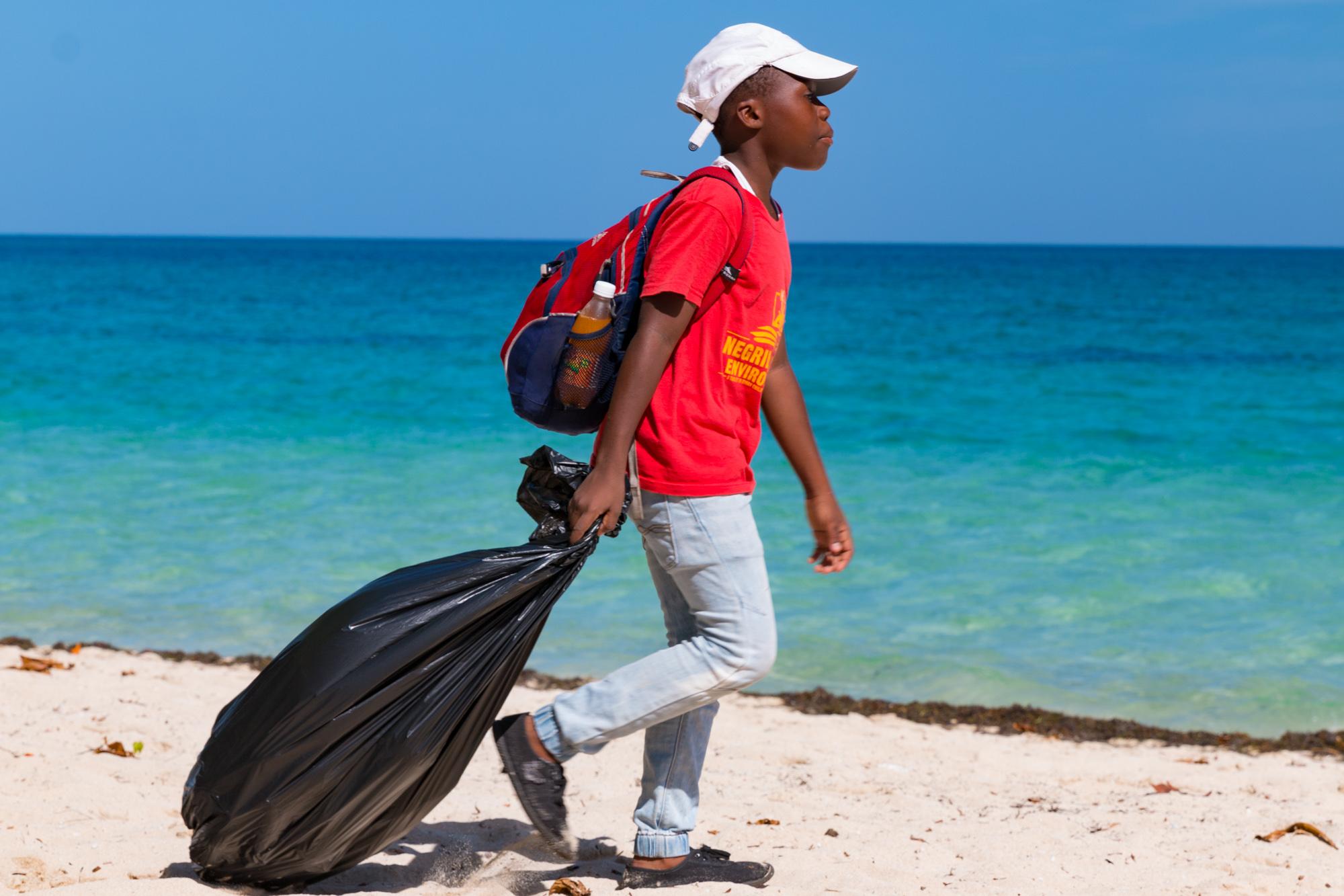 Student hauling bag of Garbage