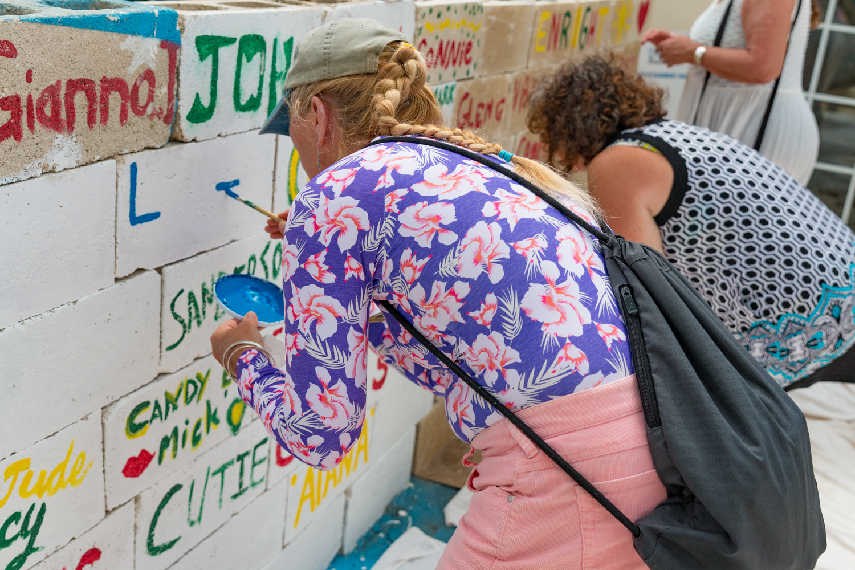 Woman writes name on brick