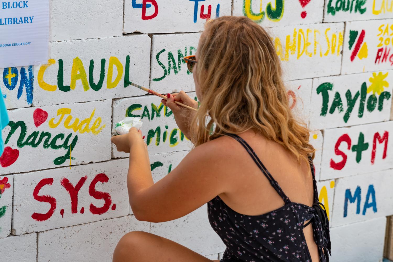 Woman writes her name on brick